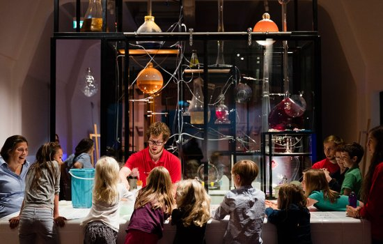 A group of children watch an explainer carry out an experiment at the Chemistry Bar in the Science Museum's Wonderlab gallery