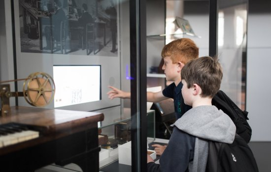Two students look at objects in the Information Age gallery