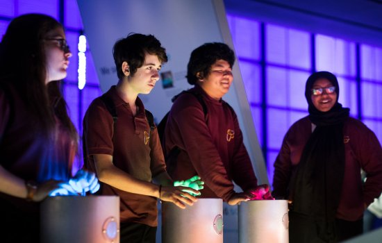 A group of school students use the interactive exhibits in the Engineer Your Future gallery