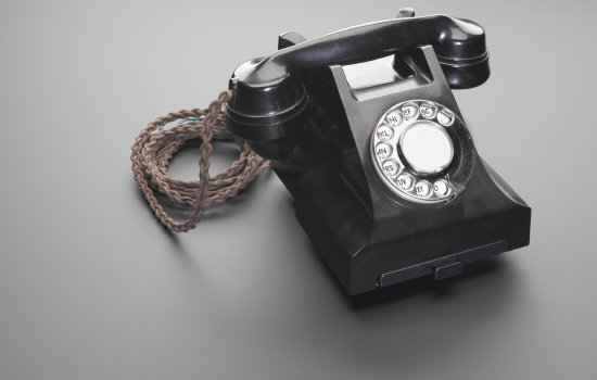 1950s rotary telephone (model 700F black C56/1) against a light grey background