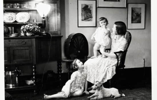A snapshot photograph of a mother and her children listening to the radio, taken by an unknown photographer in about 1930.