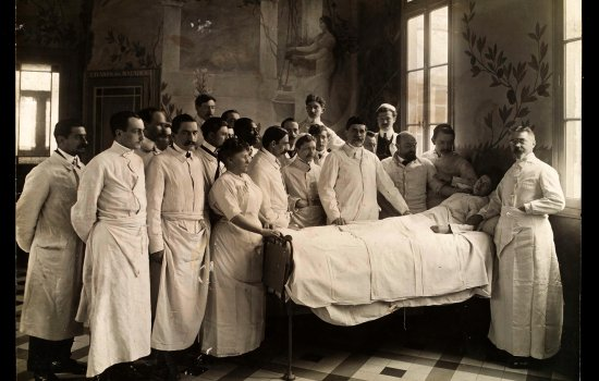 Doctors standing around a woman lying in bed in a hospital ward