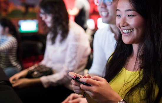 A young woman playing a game at Power Up at the Science Museum. A young man looks over her shoulder.