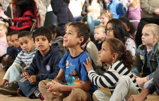 Children sat on the floor looking up