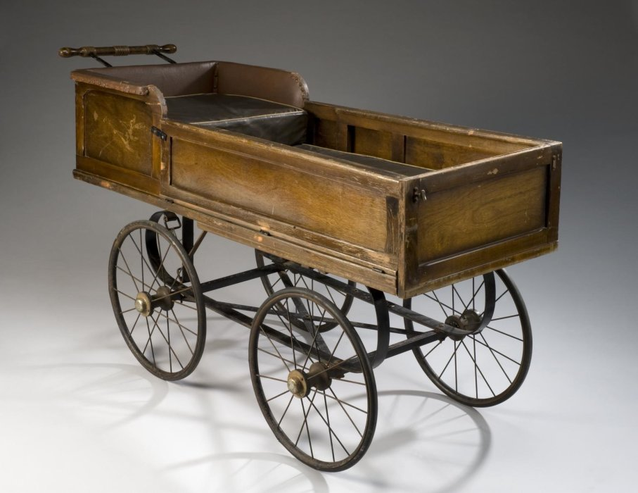 A wooden carriage with the interior padded with leather and four wheels