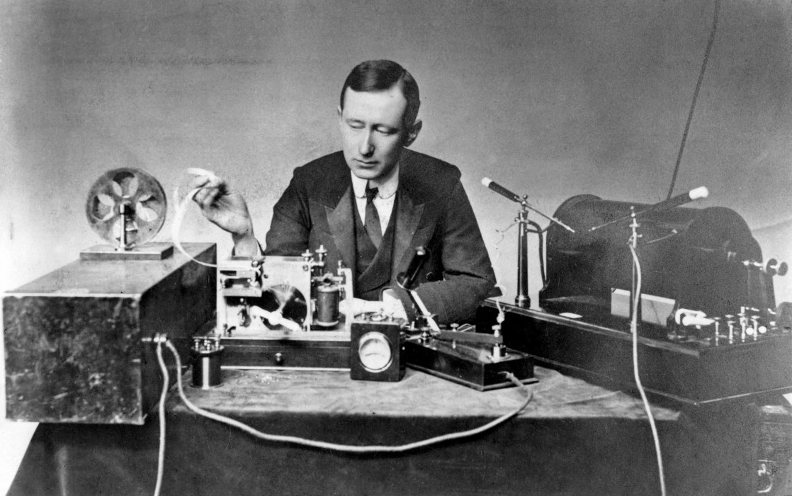 Photograph of Guglielmo Marconi sitting at a table with radio equipment, c.1902