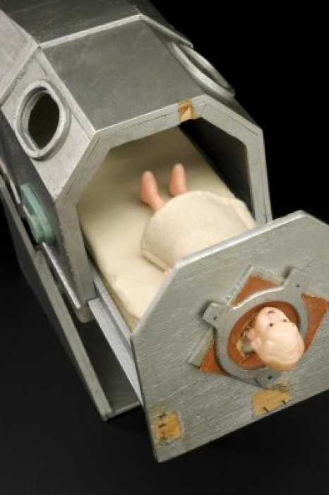 A doll in a model of an iron lung