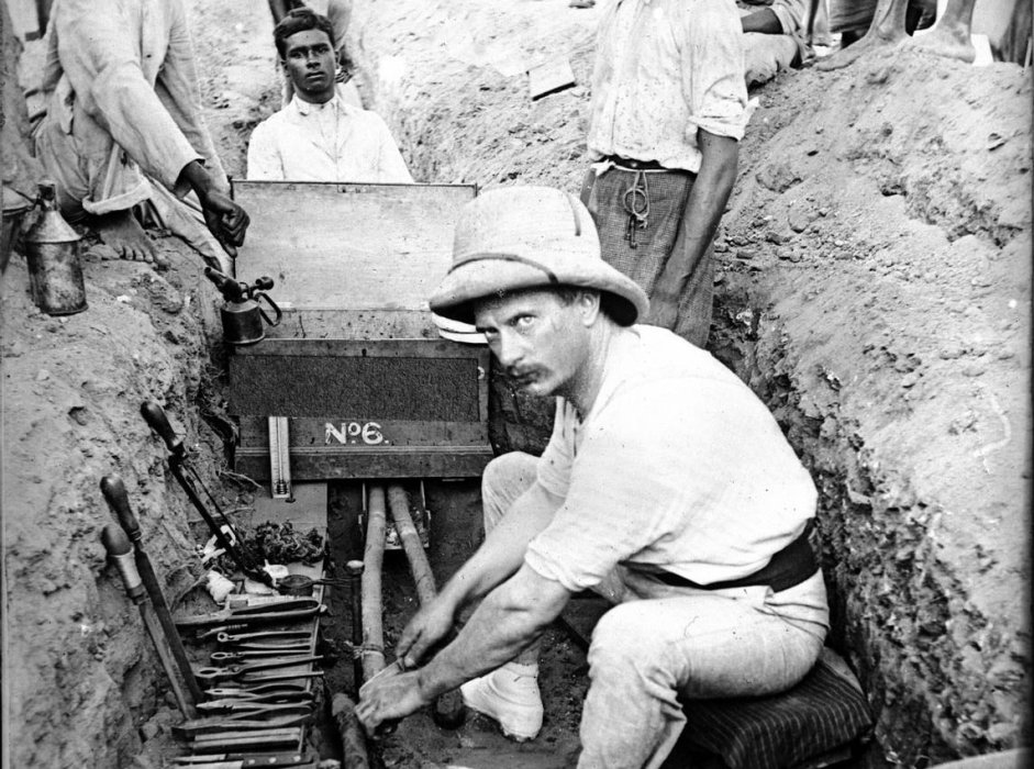 Man in pith helmet making cable joints, Madras, India