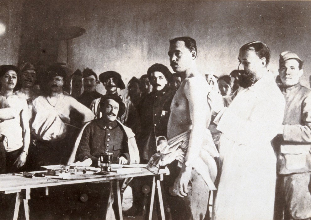 Soldier being vaccinated by a doctor in white as other men queue up behind
