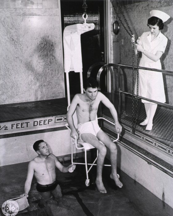 a polio patient being lowered into a swimming pool for rehabilitation exercises as a nurse observes