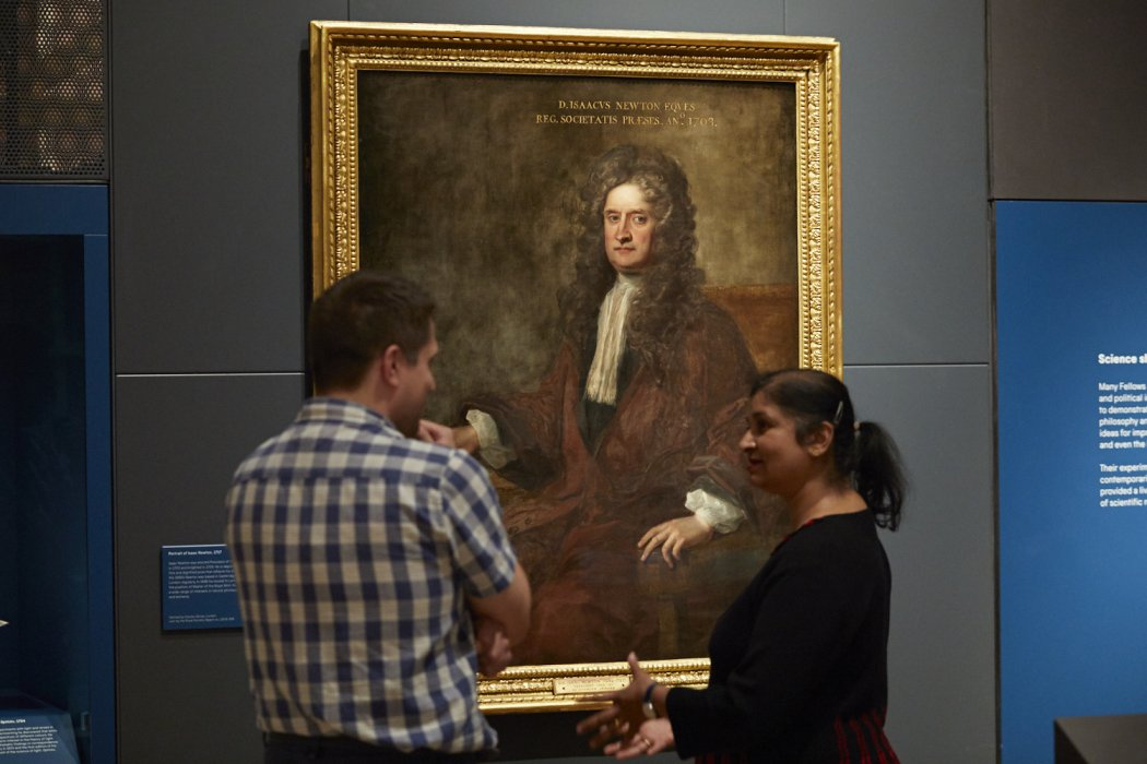 two people look at a large oil portrait on Isaac newton in a gallery with blue walls