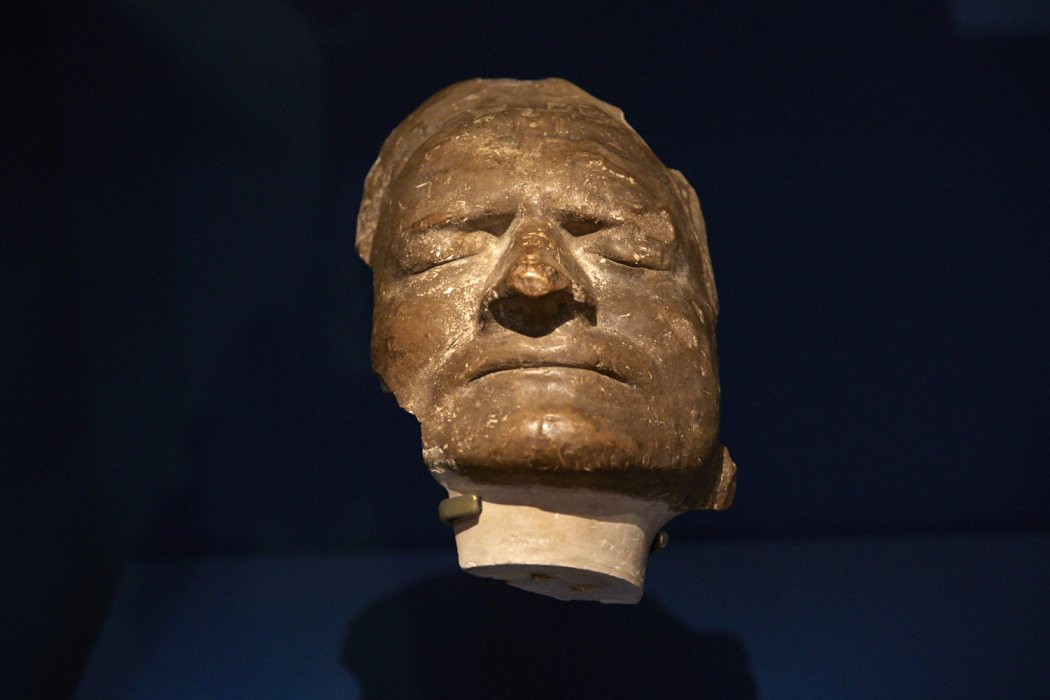 A death mask on a dark background, the mask is at a slightly tilted towards the viewer