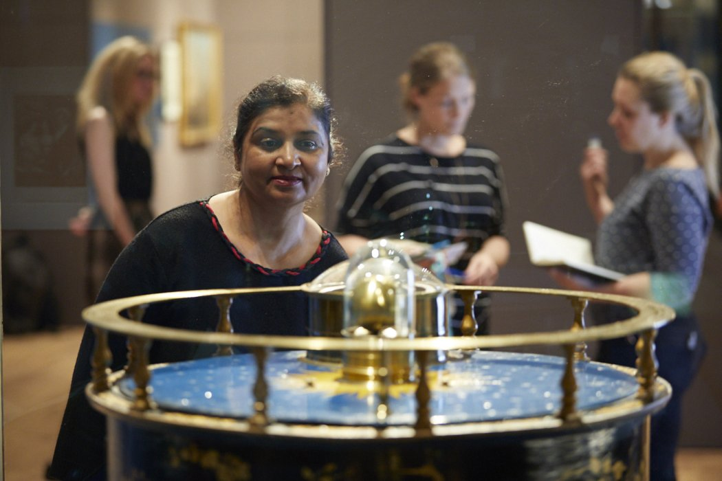A woman looking at a decorate Orrery which is dark blue and gold
