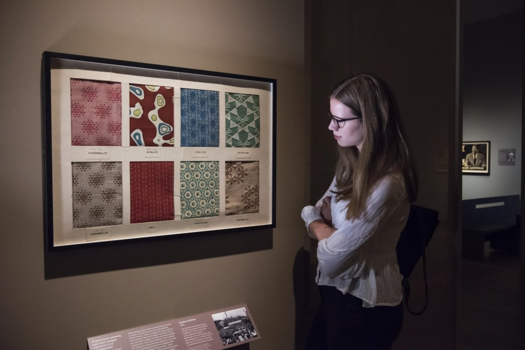 A visitor admires fabric samples inspired by X-ray crystallography in The Art of Innovation exhibition