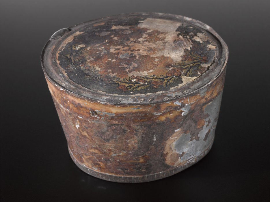 Rusty cylindrical tin against a black background