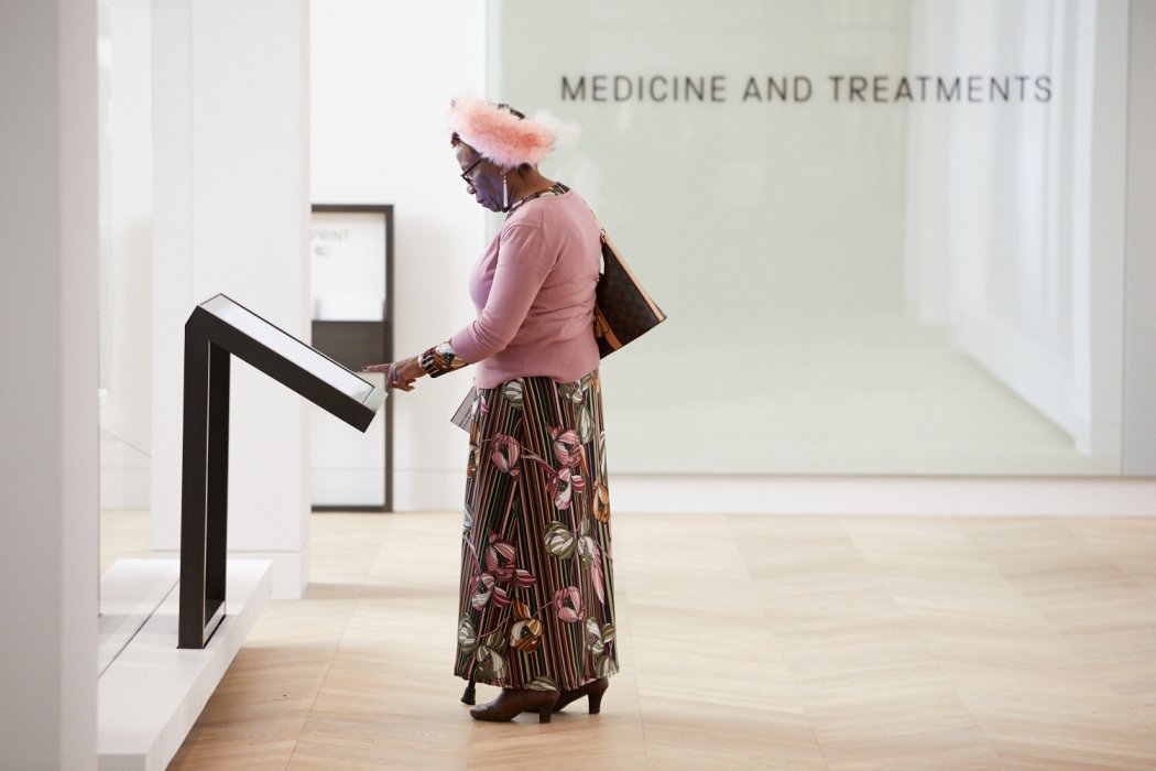 Woman reading from interactive display in the Medicine and Treatments gallery.
