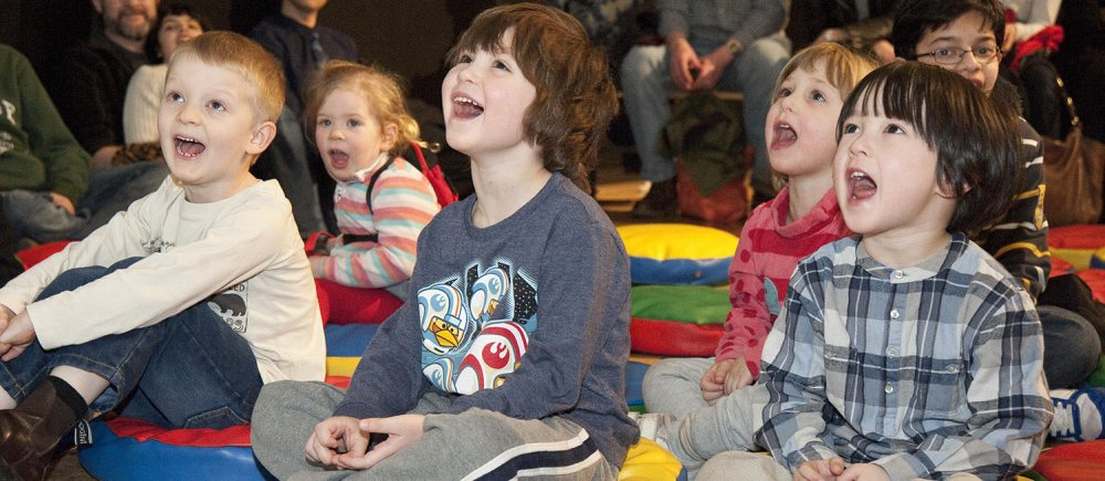 A group of children shout during an interactive storytelling session