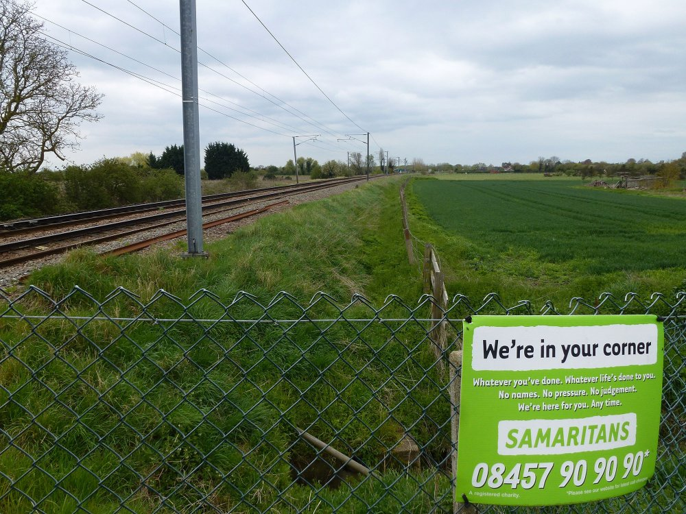 Samaritans sign next to a level crossing near Waterbeach, Cambridgeshire
