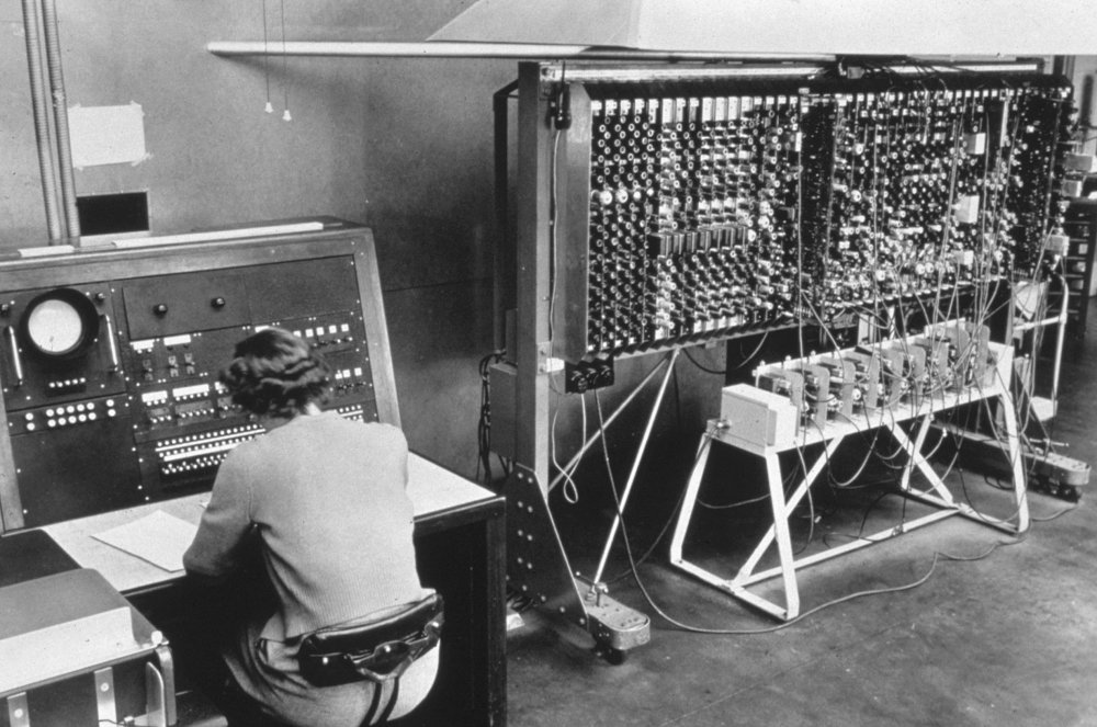 Female operator sitting at the general control console and chassis of the pilot ACE computer, 1950.