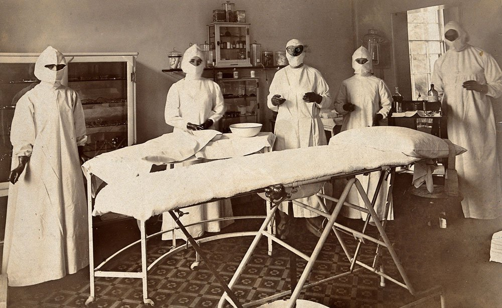 Black and white photograph of staff in surgical gowns masks and gloves in an operating theatre