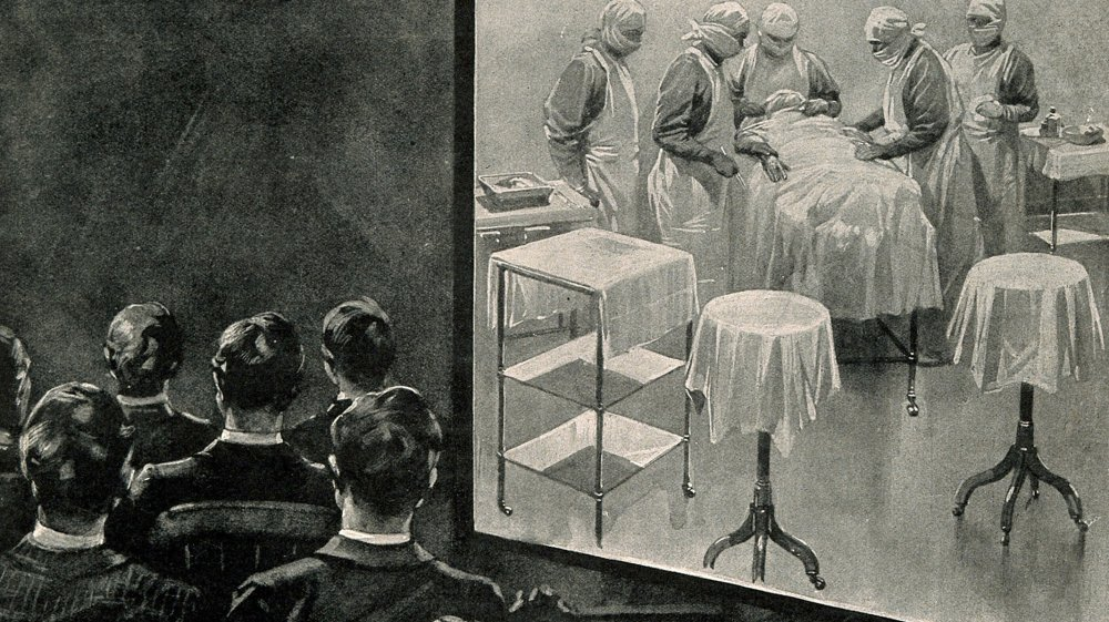 Medical students observing a surgical operation on a screen