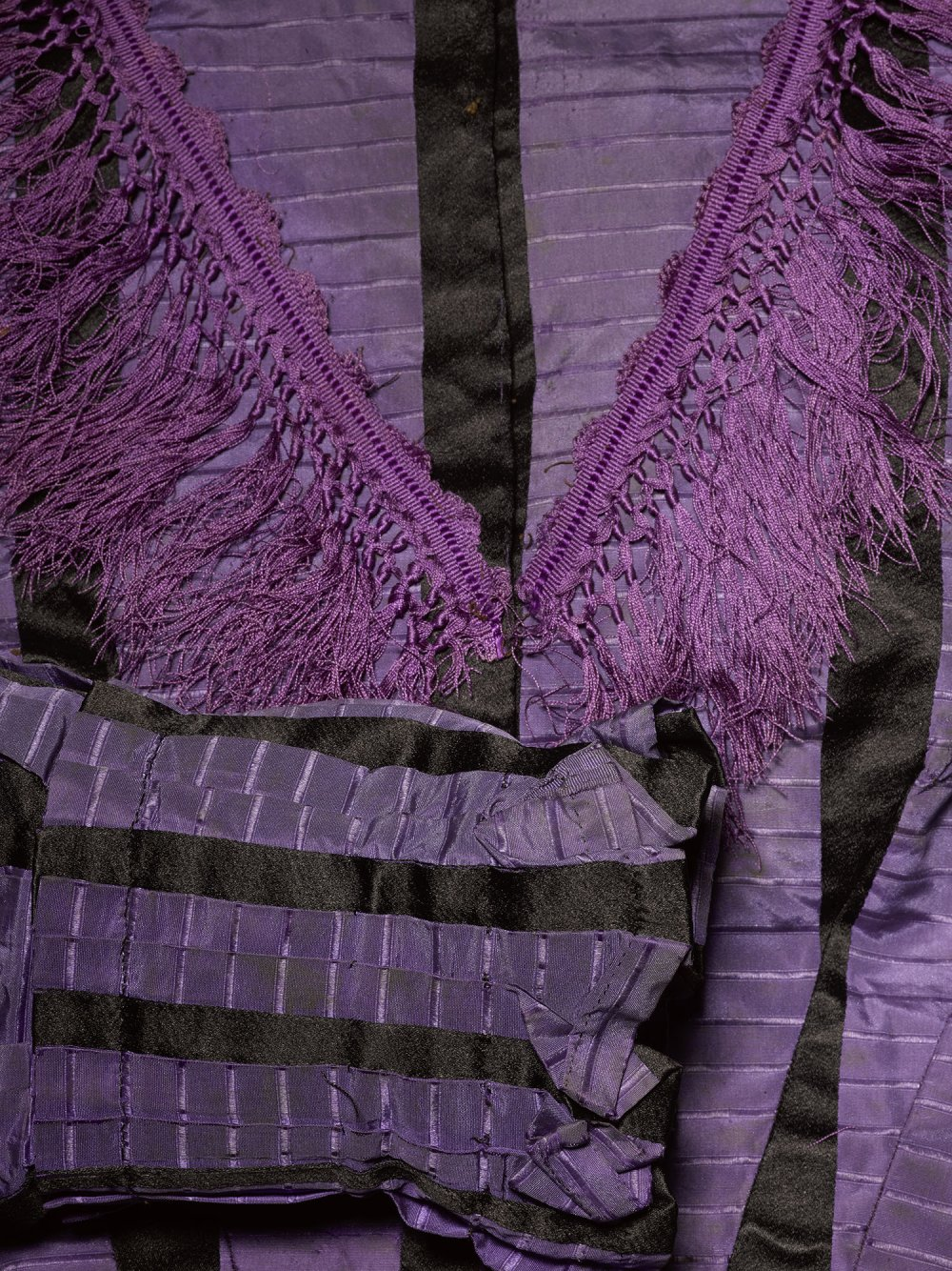 Detail of fringing and sleeve on a purple dress dyed with Perkin's mauveine dye c.1862