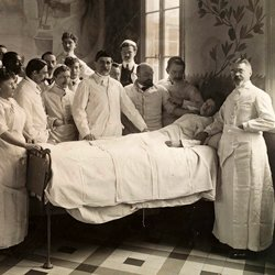 Medical staff standing around a patient in bed during a ward round