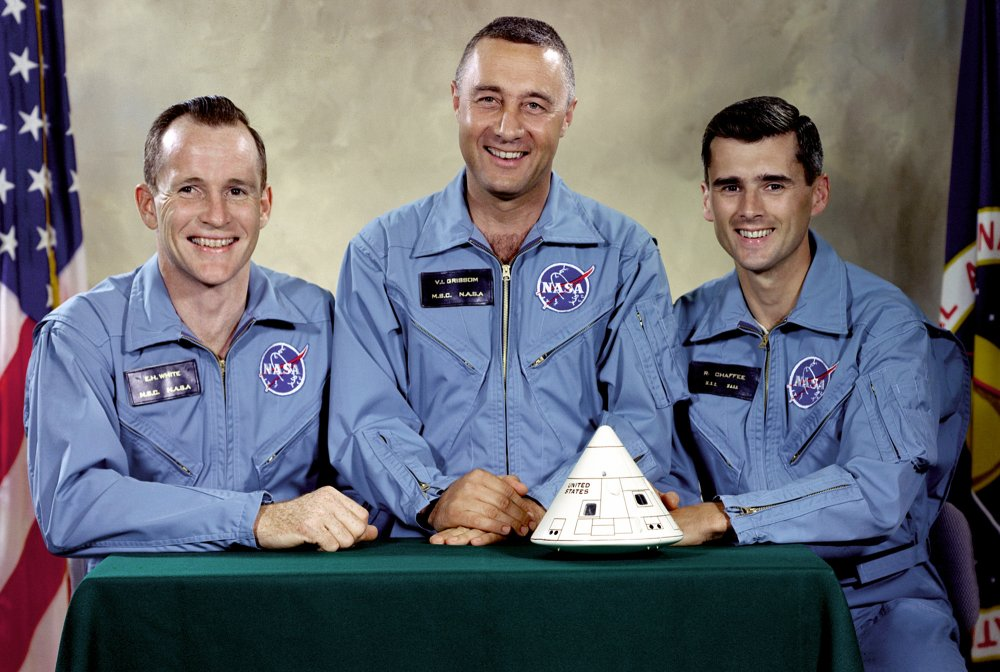 A portrait photograph of three male astronauts - they are dressed in blue and sitting behind a table with a model spacecraft on it