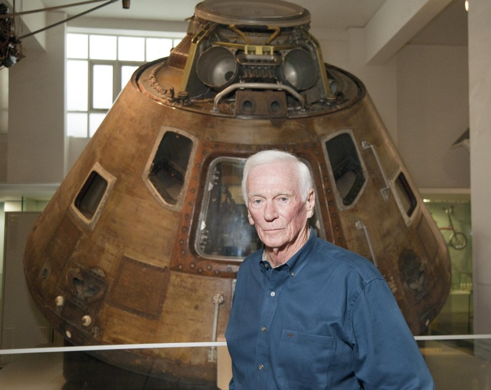 A man - astronaut Eugene Cernan - stands in front of Apollo 10 at the Science Museum in London