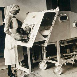 A nurse standing next to a man encased in an iron lung ventilator