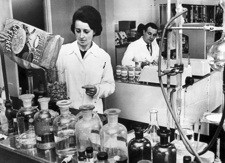 Woman in a white coat measuring out cornflakes in a scientific laboratory